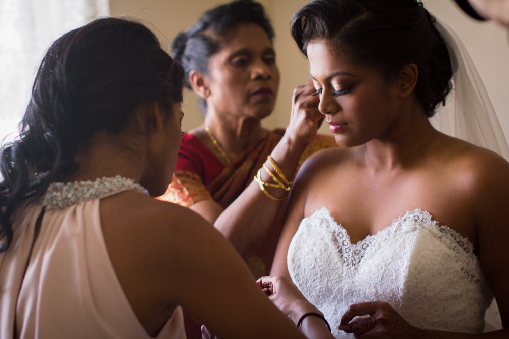 Claudia's sister and Mom helping her with her wedding dress and the finishing touches.